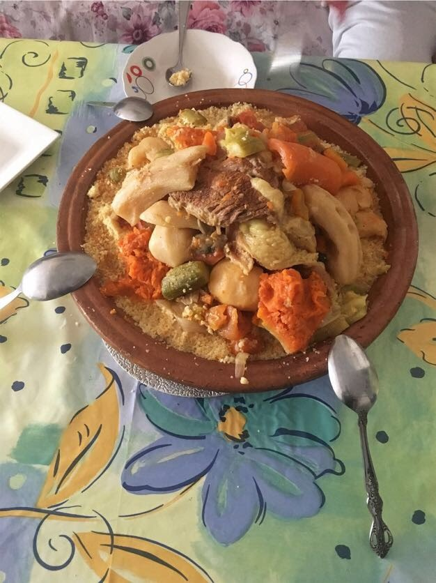 A tagine filled with Friday couscous, piled high with vegetables and eaten communally (hence the spoons on the edge – totally optional!). Photo Credit: Mallory Mrozinski, Spring 2018.