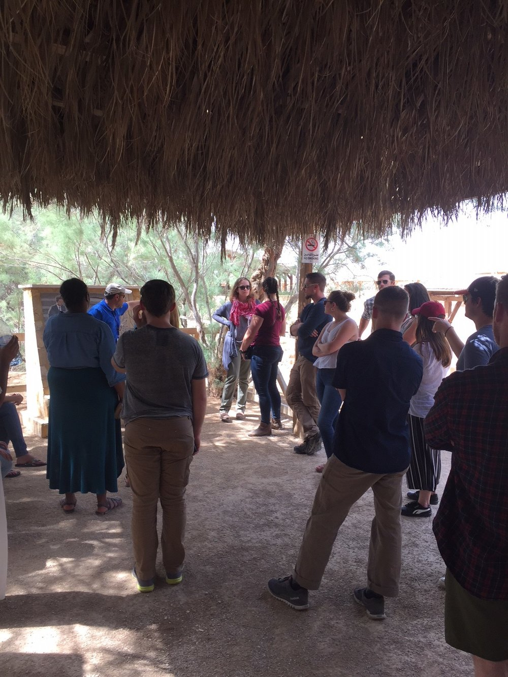 Spring 2018 students gather around the tour guide to hear about the place of Jesus' baptism.