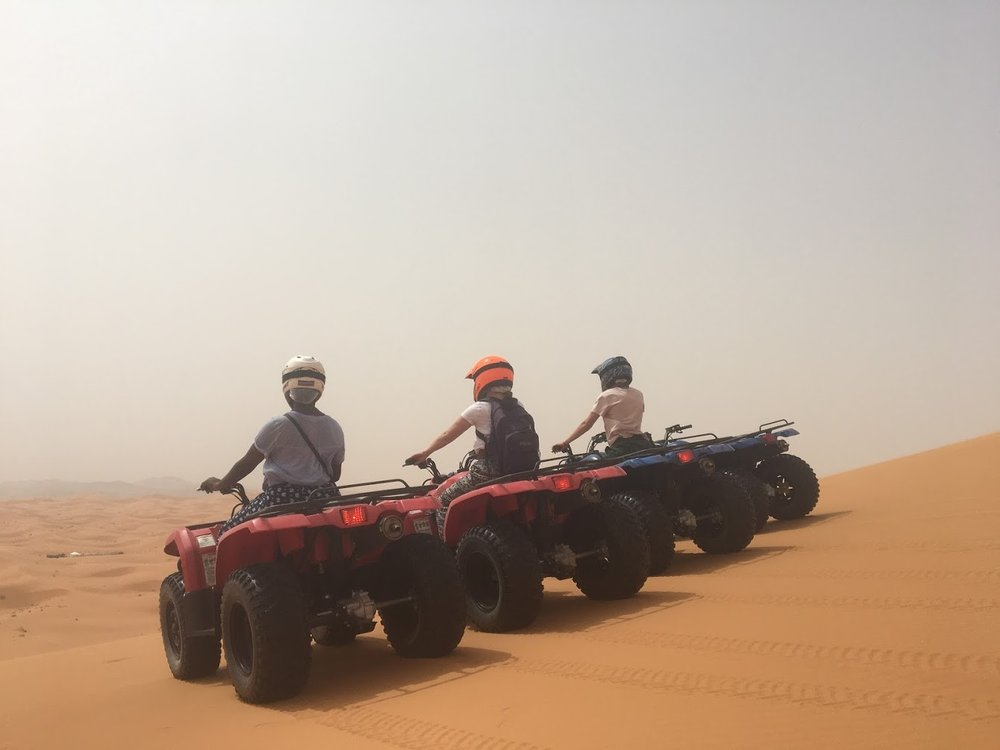 In the past, I ATV'ed in a rainforest which was an incredible experience. However, getting to ride an ATV in the middle of the Sahara Desert was by far the coolest thing I've ever done in my life. My friends and I hopped onto our ATVs and raced up and down multiple sand dunes. After about 30 minutes of riding through the desert, we took a quick break to take this picture. As we were relaxing, we thought we were going to turn around and go a different route but alas we were mistaken. After taking a few sips of water and capturing some pictures, our guide proceeded to drive down this enormous sand dune. The drop was about 100ft-- almost straight down. As I slowly inched my way to the edge, I was sure my ATV was going to flip over and I was going to go rolling down this dune, but at the same time, adrenaline was running through my veins and I was excited about going down. One by one, we all rolled down on our ATVs until we reached the bottom. Then, we hit full throttle and continued our adventure. Photo Credit: AMIDEAST, Summer 2018