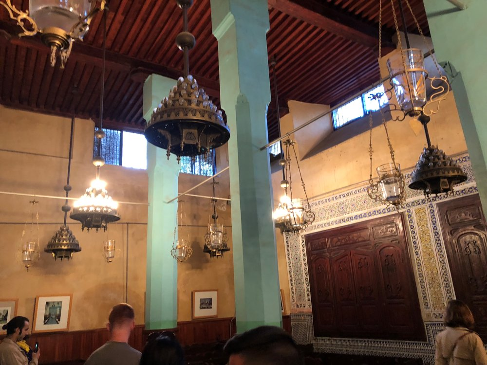 """Also in Fes, but in the Jewish Quarter, we visited an old Jewish synagogue. This synagogue is extremely interesting because the Moroccan architectural influences can be seen in certain tilework, but it differs from the """"look"""" of a mosque in the format of the interior. My favorite part of this synagogue was a hole in the floor that revealed a well and a small pool of water in a room below the synagogue. We learned that this was used for women before they got married. They would go into the water while their friends and family shouted blessings and happy phrases from the hole in the ceiling above. In such a heavily Islamic country, learning about this history of Judaism particularly in this synagogue was extremely fascinating. Photo Credit: K. Meacham, Fall 2018"""