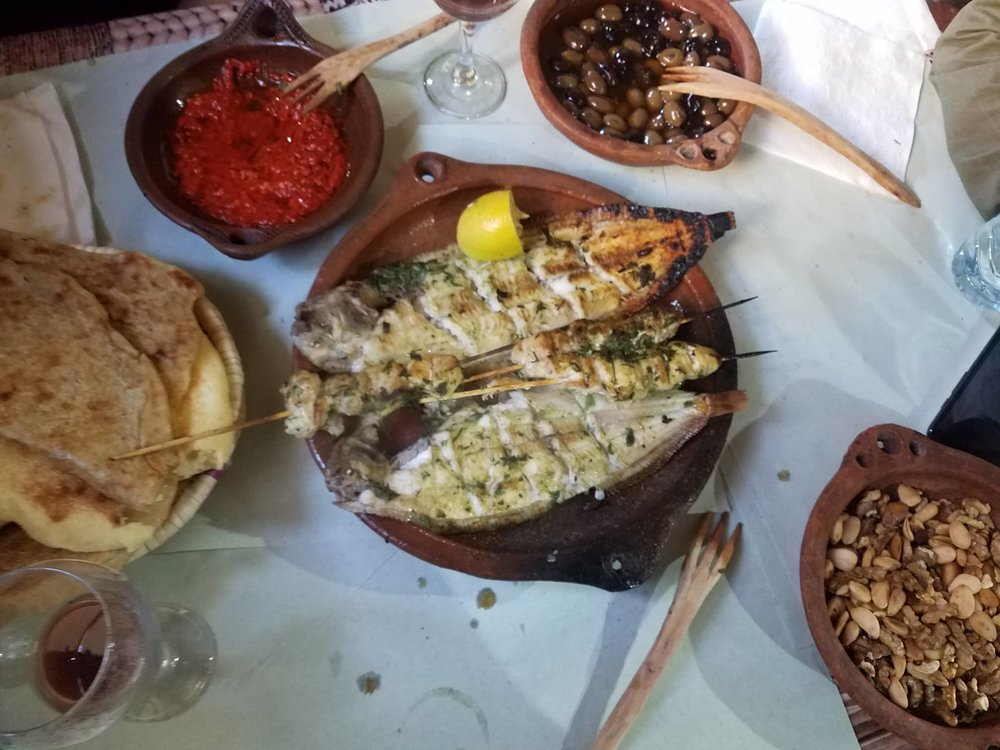 The seafood restaurant where we ate lunch, including the main dish with a spicy red sauce, bread, olives, and nuts to complement all of the plates. Photo Credit: Ashley Lasiter 2018.