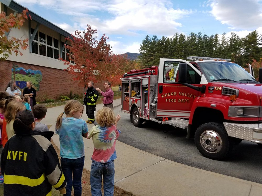 Parents and Faculty introduce themselves as volunteer fire fighters to the local students
