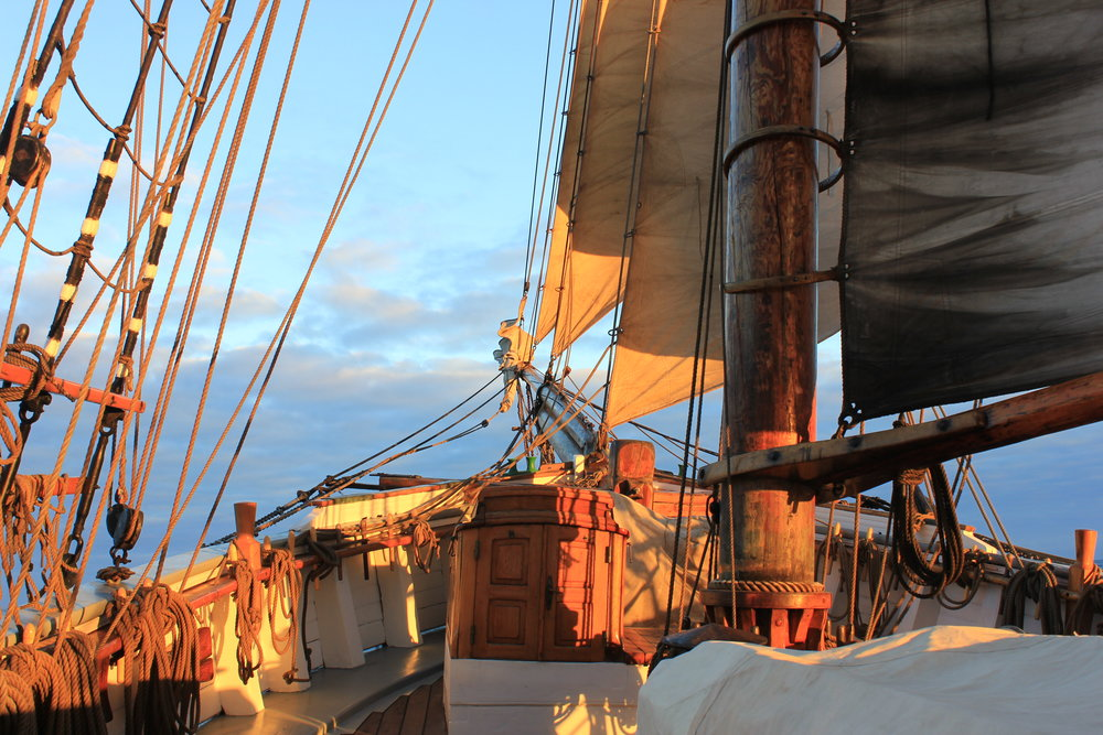The sun setting over the sails and foreship whilst underway to Tenerife, Canary Islands, from Madeira. June 2018.