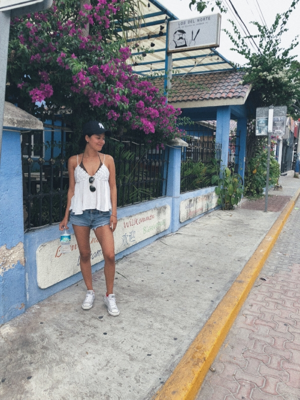 A stylish girl in sports clothes walking on La Quinta Avenida (or Fifth Avenue) in Playa Del Carmen, Mexico