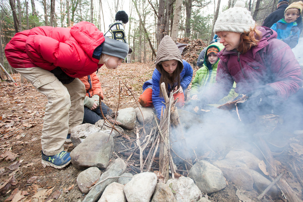 Fourth graders Elan, Margaretta, and teacher Annie work on the fire.