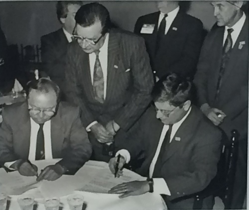 Kazakhstan's Minister of Finance Yerkeshbay Derbisov and Dan Witt sign an agreement to launch ITIC in March 1993, while State Revenue Administration Director General Marat Ospanov looks on.