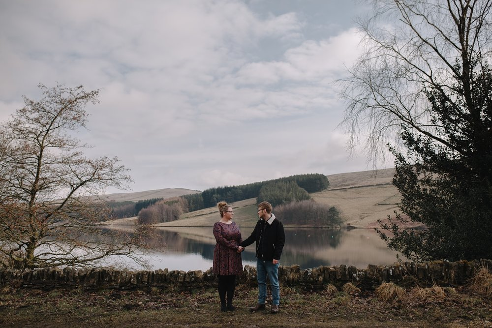 man and woman holding hands infront of eerwood reservoir and the Goyt Valley