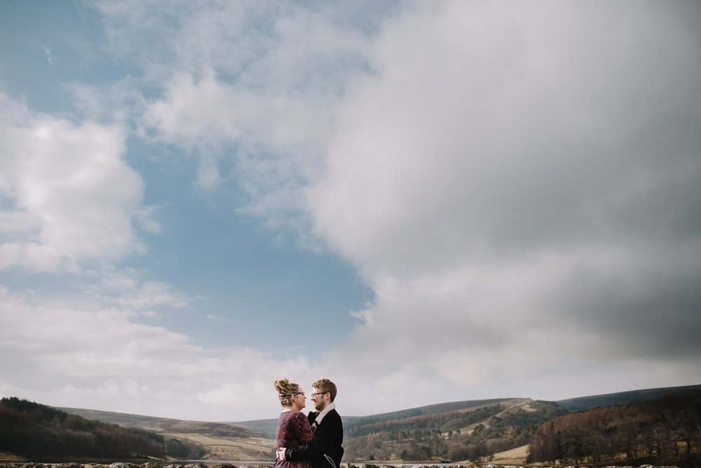 man and woman hugging with views of the Goyt Valley in the background