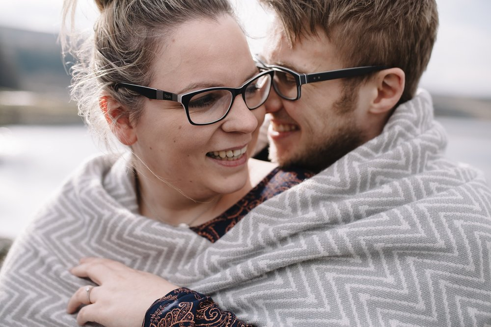 close up of man and woman wrapped in a blanket smiling and laughing