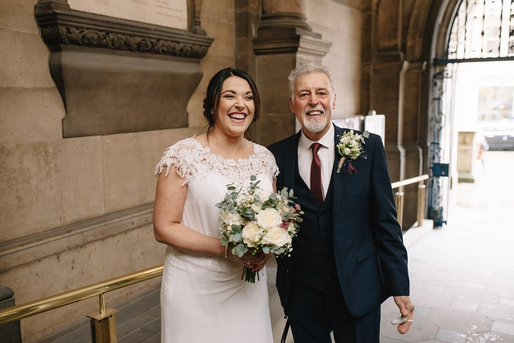 bride and father stood in the entrance of Sheffield Town Hall laughing