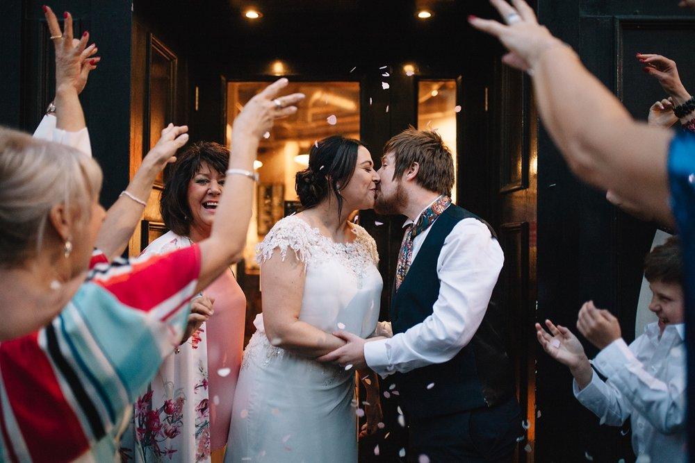 bride and groom kissing outside Couch Sheffield with guests throwing confetti
