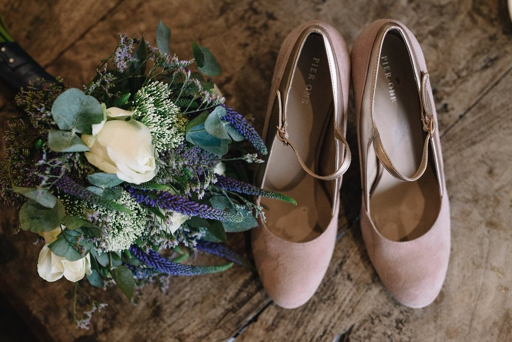 Bridal bouquet and wedding shoes on wooden table