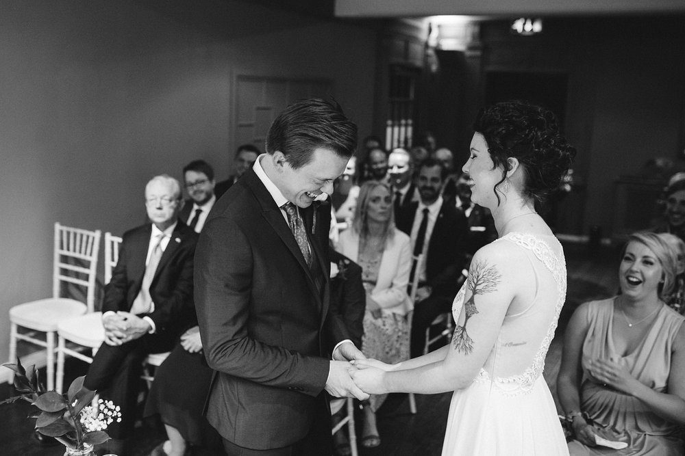 black and white photo of groom laughing whilst saying his vows