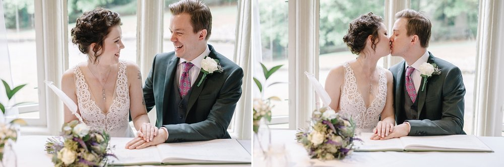 bride and groom signing the register and laughing at Whirlowbrook Hall