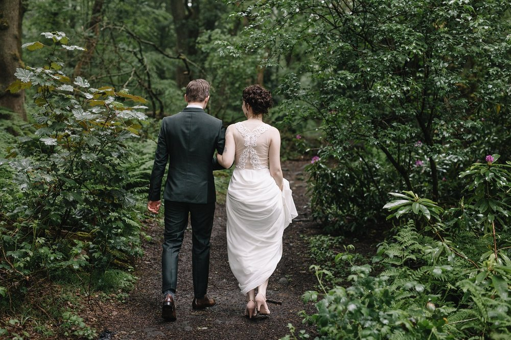 bride and groom walking through the woods at Whirlowbrook Hall