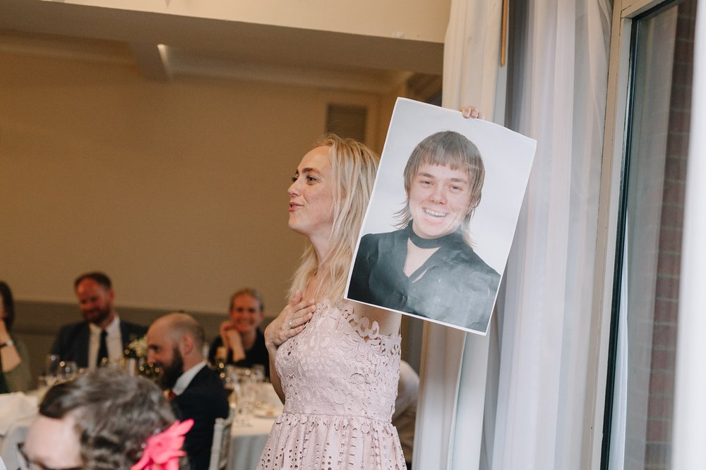 grooms sister holding up embarrassing photo of groom