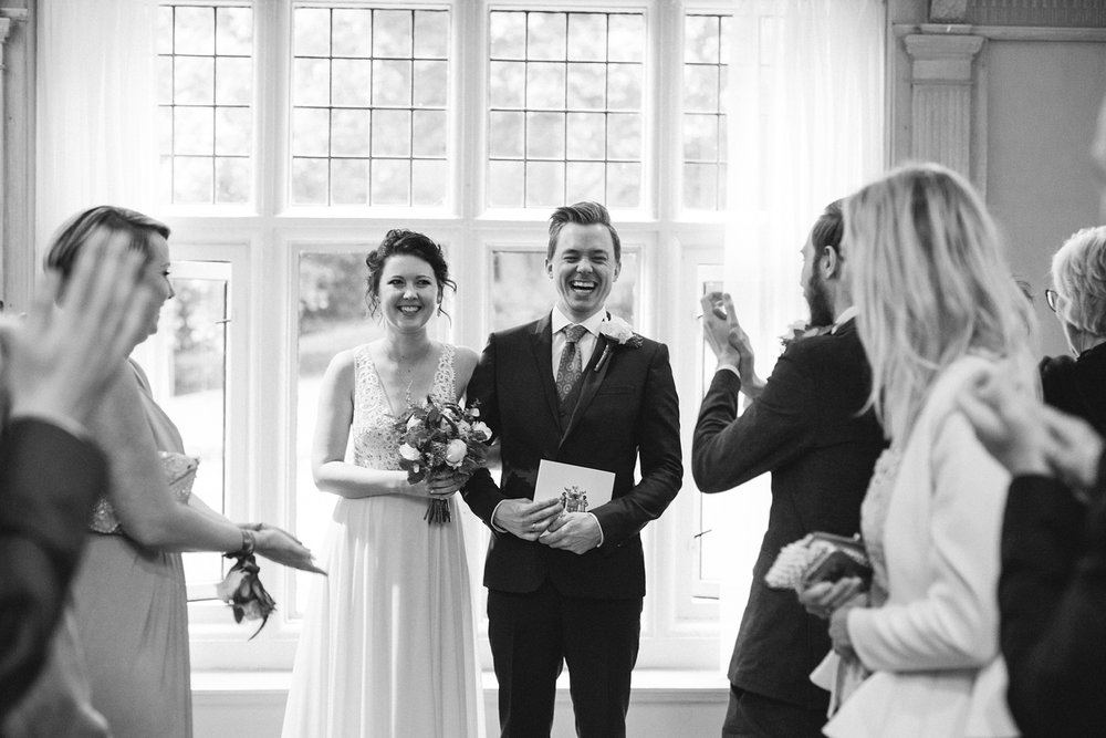 black and white photo of bride and groom holding their wedding certificate