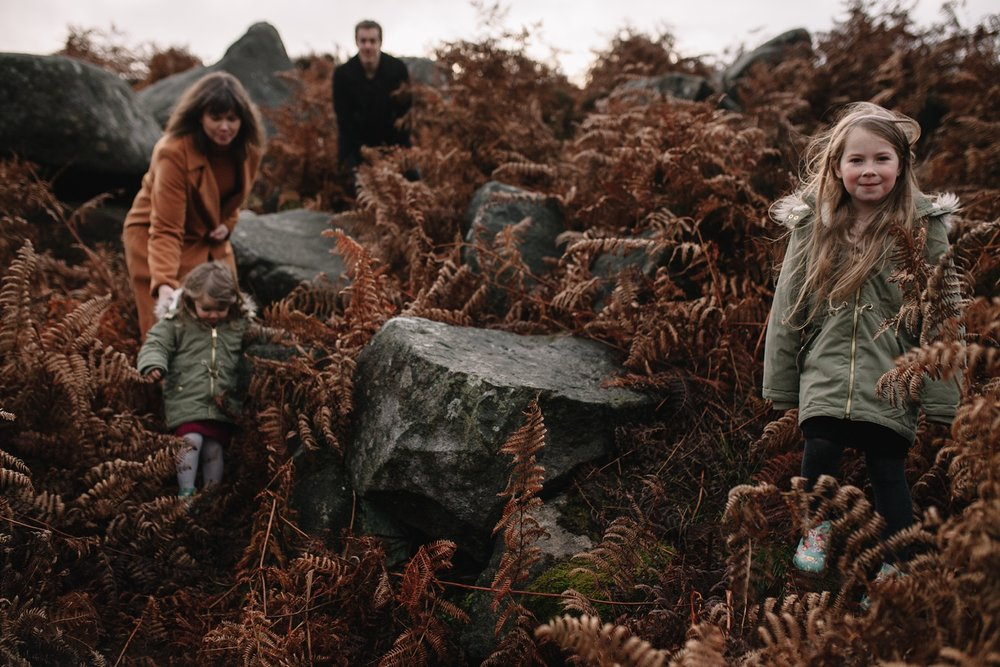 mum, dad and two little girls walking in amongst the brown ferns