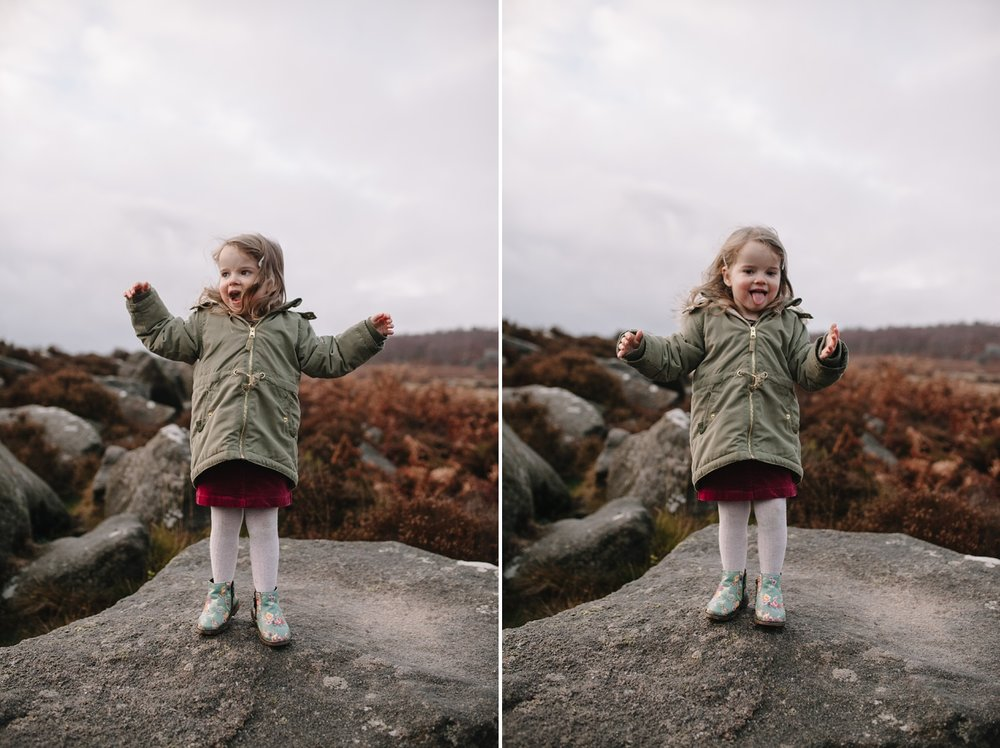 little girl jumping around on a rock smiling and pulling faces