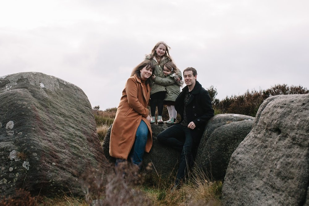 mum and dad sat on a rock with two little girls stood up beside them smiling at the camera