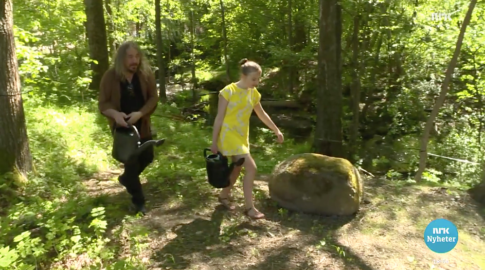 Håvard og Linnea vanner gressfrø på tomta.
