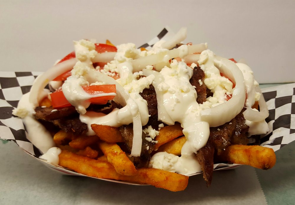 GREEK FRIES:     A bead of seasoned battered fries with melted homemade queso topped with  Greek Gyro meat (lamb and beef) fresh onions, tomatoes, tzatziki sauce,        topped with feta cheese