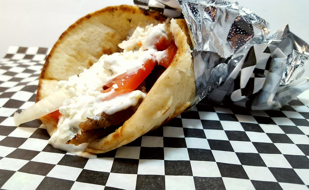 GREEK PITA (GYRO): A soft pita bread stuffed with   Greek gyro meat (lamb and beef), fresh onions, tomatoes, tzatziki  sauce, topped with feta cheese.