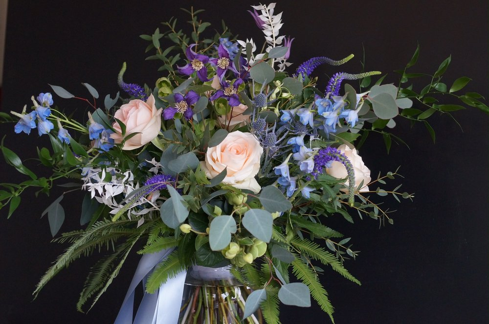 Bridal bouquet gets the blues - delphinium, clematis, veronica and eryngium are set off with various foliages and a little of the oh-so-trendy bleached ruscus.