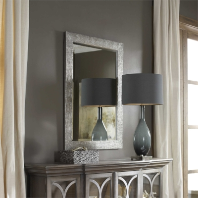 Detailed metal mirror and jewelry box, ceramic lamp, soft window treatments, wooden cabinet. Texture diversity.
