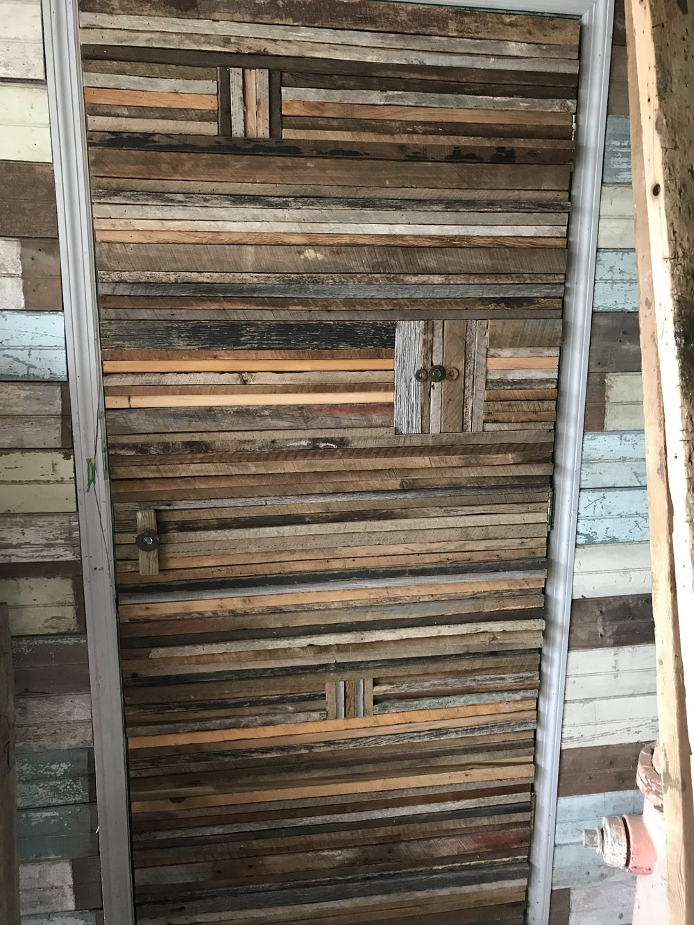 Reclaimed barn wood used to create a unique cover for a door