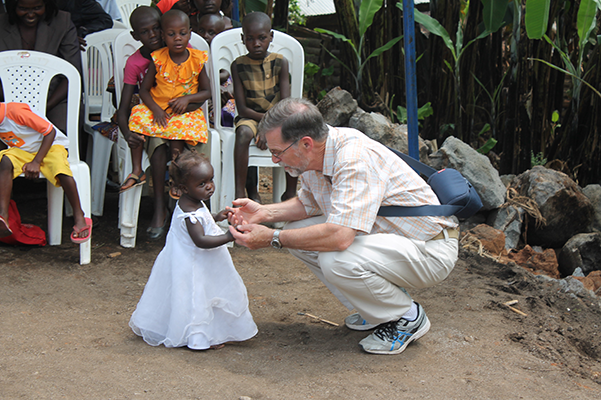 Pastor Bruce Van Dusseldorp, US Director for ChristAid International and former CCC pastor, with a small child in Uganda.
