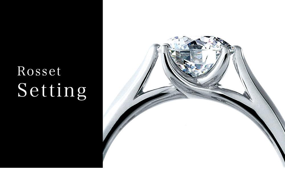 ロゼットセッティング - 美しいプリマドンナの指先から発想を得た優美な爪のデザイン「ロゼットセッティング」は、指につけた時、ダイヤモンドにあらゆる角度からの光を受け止める様、設計されています。ダイヤモンドの露出面積を最大限に、爪部を極力減らし最高の輝きに貢献する、最もシンプルで美しいデザインに完成されました。