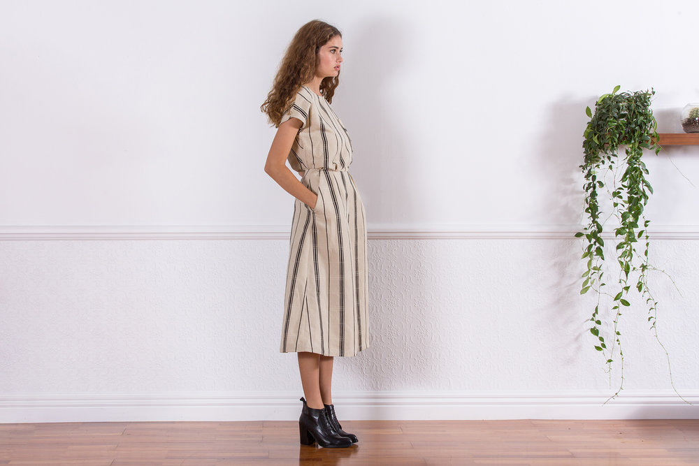 indoor fashion photo shoot of girl in white stripe dress