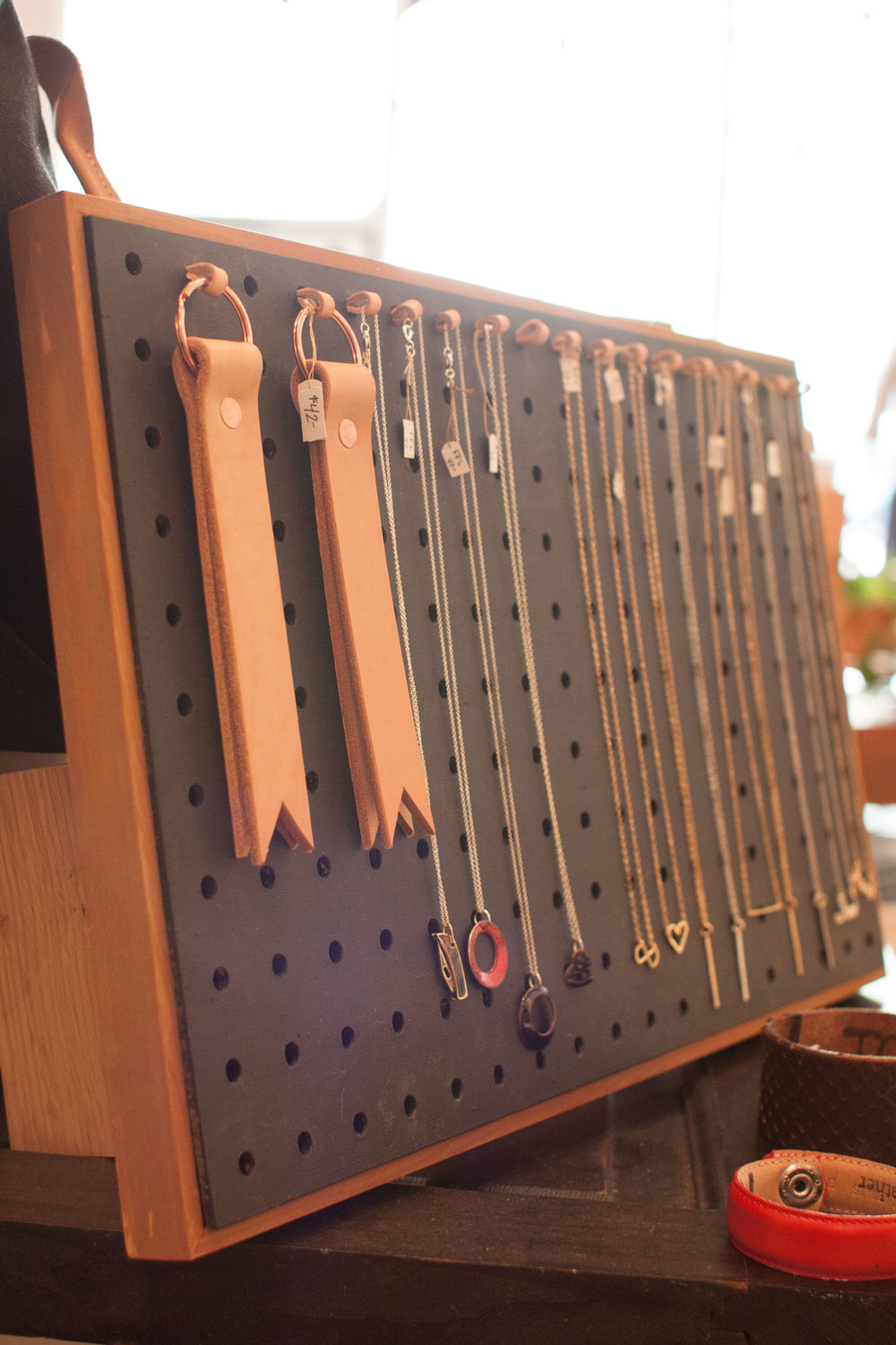 Various handmade pieces of jewelry are organized by small leather straps Chika made to attach to pegboard. It's the little things.