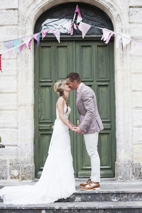 Bride and groom kissing outside the doors of the château