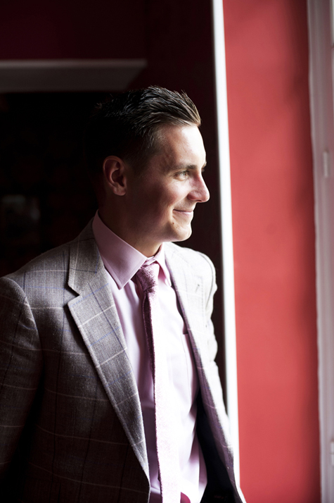 Groom looking out of window before wedding service, dressed in a Paul Smith suit