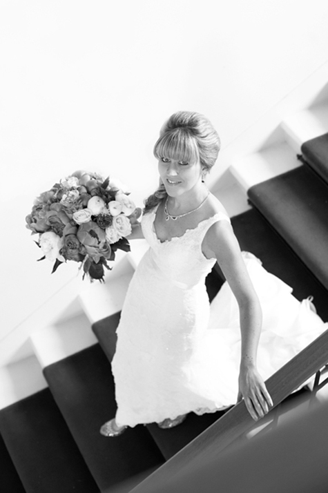 Bride on stairs holding bouquet, in a dress by Cymbeline