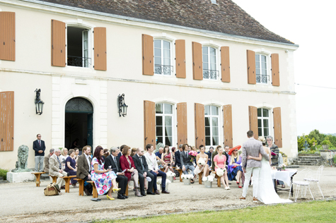 Exterior shot of château and wedding party during wedding ceremony