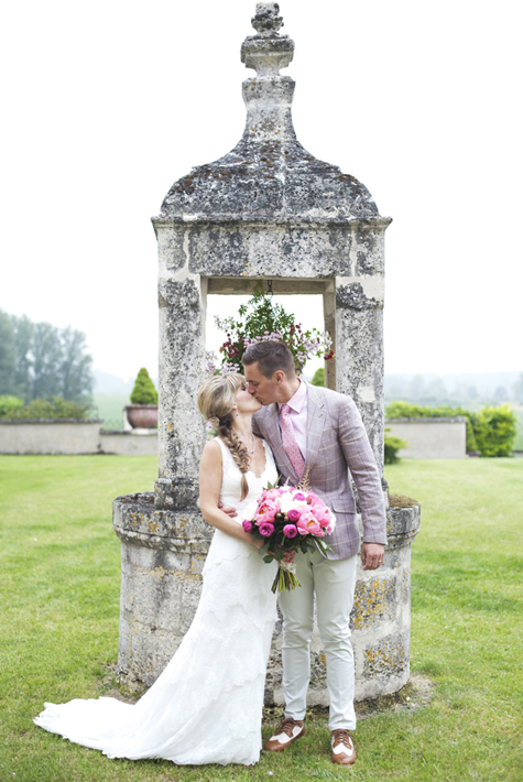 Bride and groom kissing by an old well