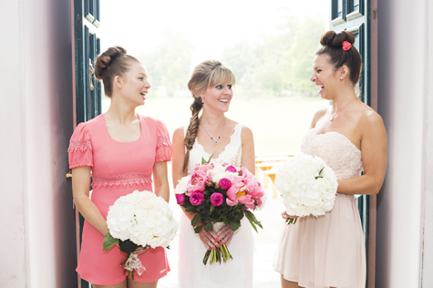 The bride and her two bridesmaids with bouquets laughing