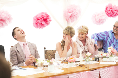 Groom laughing with bride and bride's mother during speech