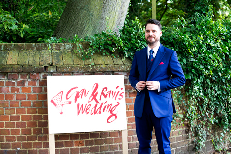 Groom standing next to 'Gav and Ravi' wedding sign