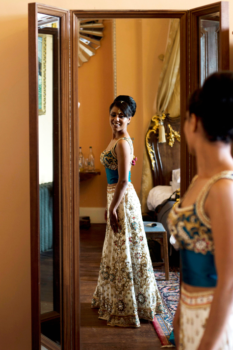 Full-length shot of bride smiling reflected in mirror in wedding outfit