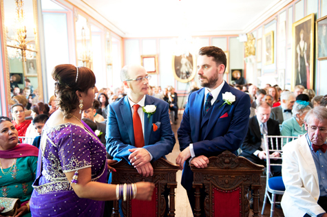 Groom standing next to best man leaning on chairs in venue talking to mother of bride
