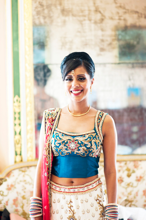 Portrait shot of bride in full wedding outfit smiling radiantly