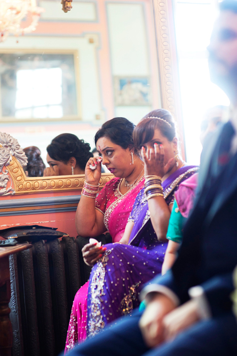 Bride's mother and relative at wedding wiping away tears during ceremony