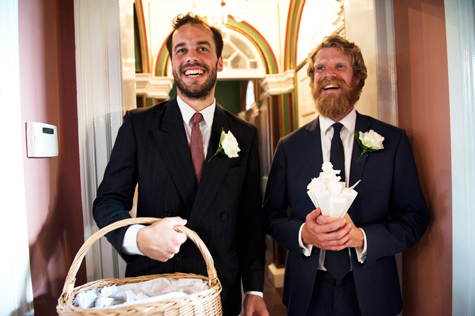 Two of the grooms men laughing, one holding confetti basket