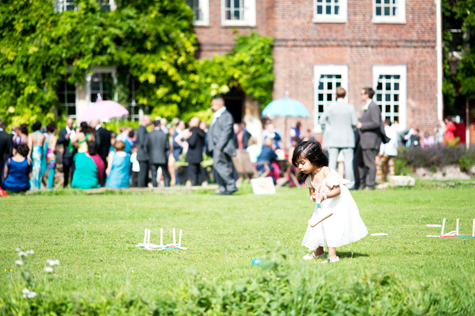 Exterior shot of guests and little girl with croquet stick on the lawn