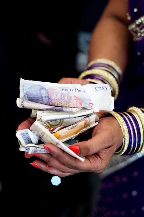 Detail shot of bride's hands holding banknotes, gifts of money