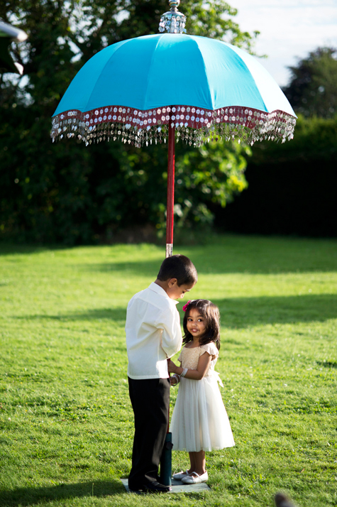 Exterior shot of young boy and girl standing under a turquoise parasol on the lawn